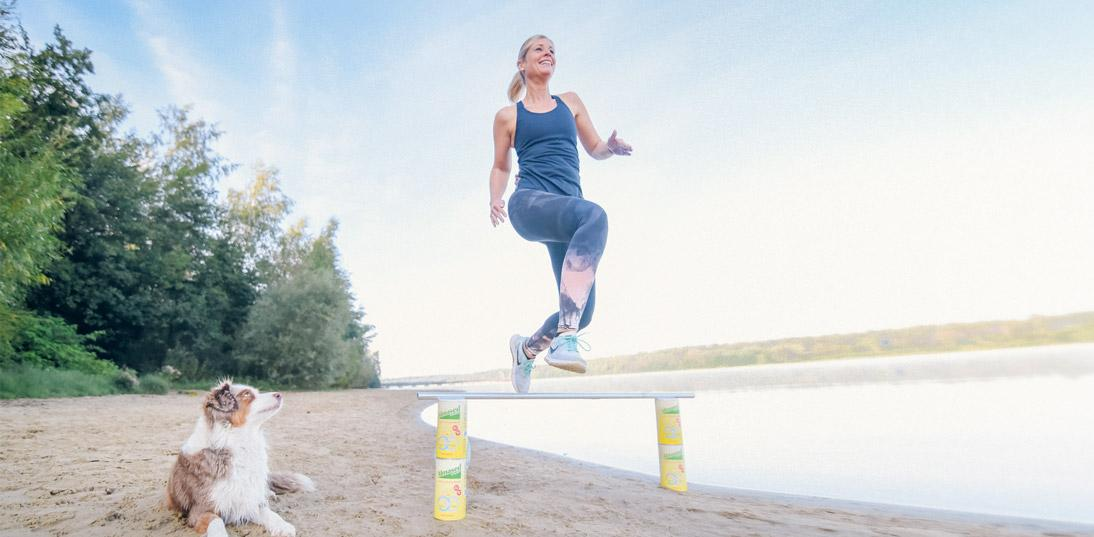 Lady jumping over bar held by cans of Almased