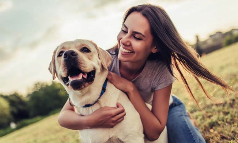 Girl smiling and hugging dog