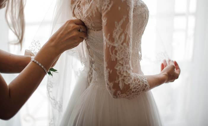 Woman having her wedding dress zipped up