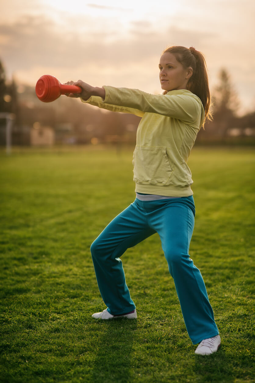 girl in a squat swinging a kettle bell